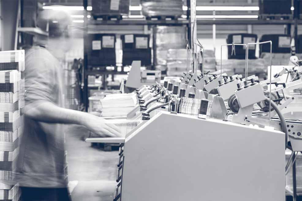Blick in die Produktionsstätte: nach dem Druck werden die Print-Produkte an der Heftmaschine weiterverarbeitet